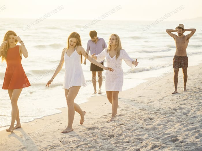 group of friends walking on the beach at sunse