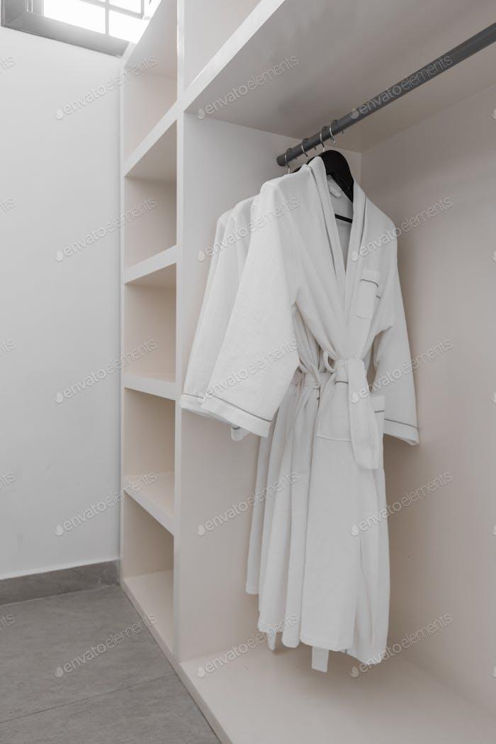weiße Gewänder mit hölzernen Kleiderbügeln in der Garderobe.