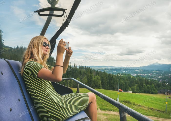 Young woman making photoes on cable car, Poland