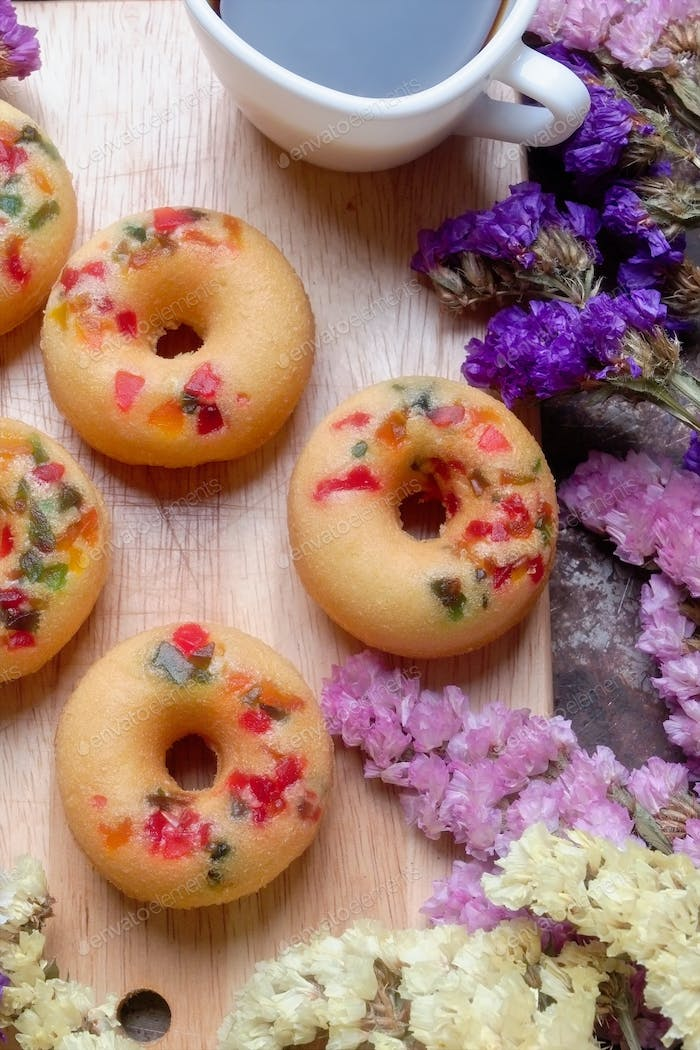 Fruity donuts with cup of black coffee