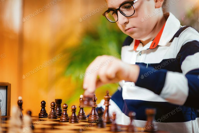 School boy playing chess