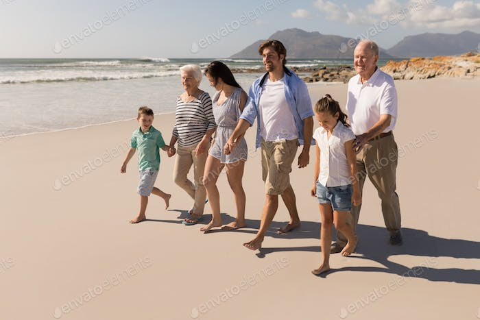 Front view of happy multi-generation family holding hands and walking on beach in the sunshine