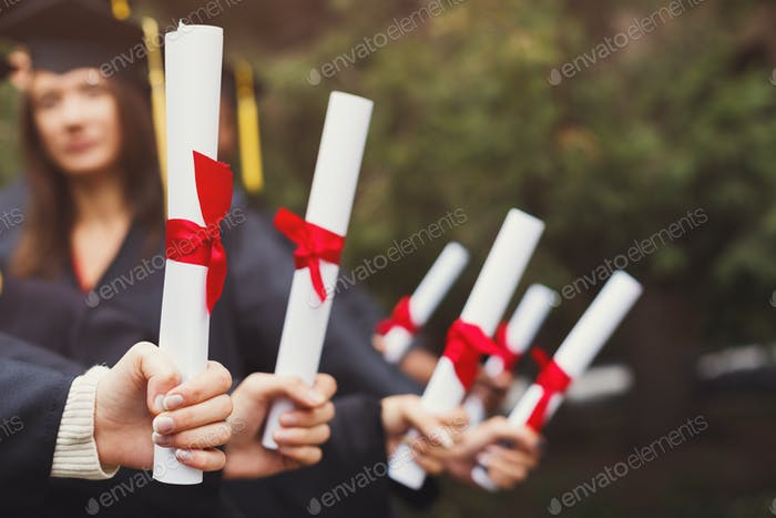 Group of students holding diplomas, copy space