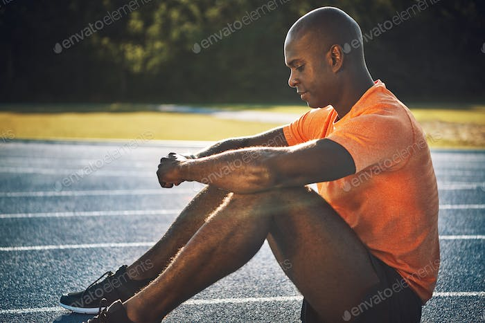 Athlete sitting on an outdoor track preparing for a run