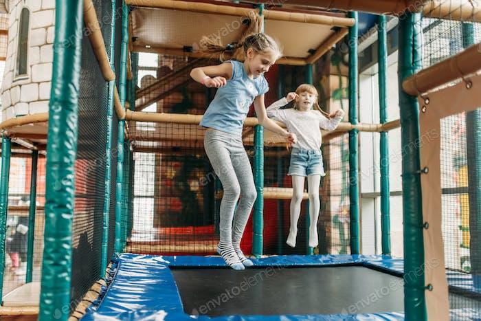 Girls jumping on trampoline, children game center