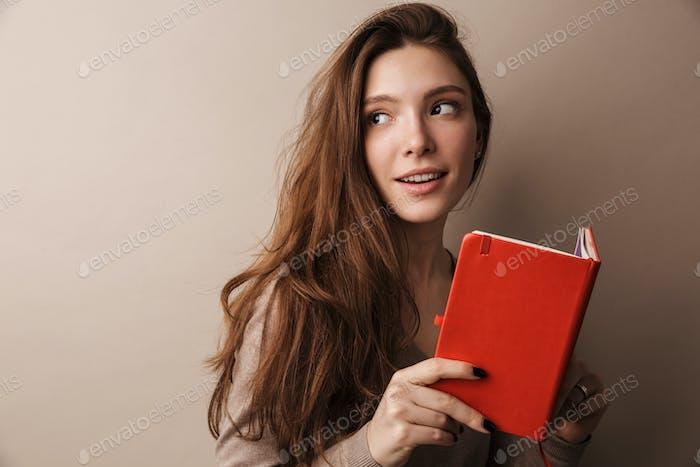 Foto von kaukasischen erfreut Frau lächelnd und hält Tagebuch