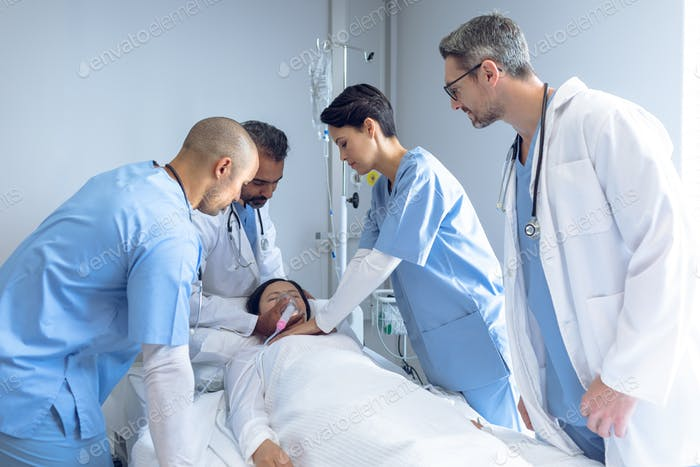 Side view of diverse doctors examining Asian female patient in bed in ward at hospital.