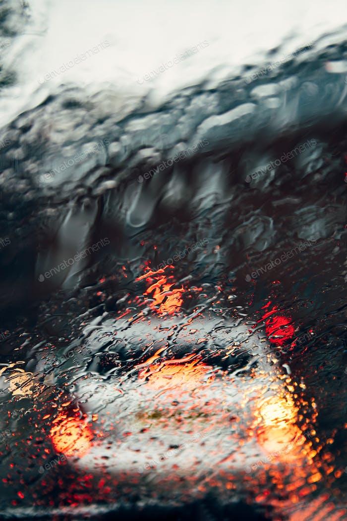 Verschwommene Stadtstraße während des dunklen Regentages