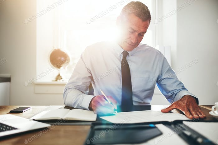 Focused mature businessman signing documents at an office desk