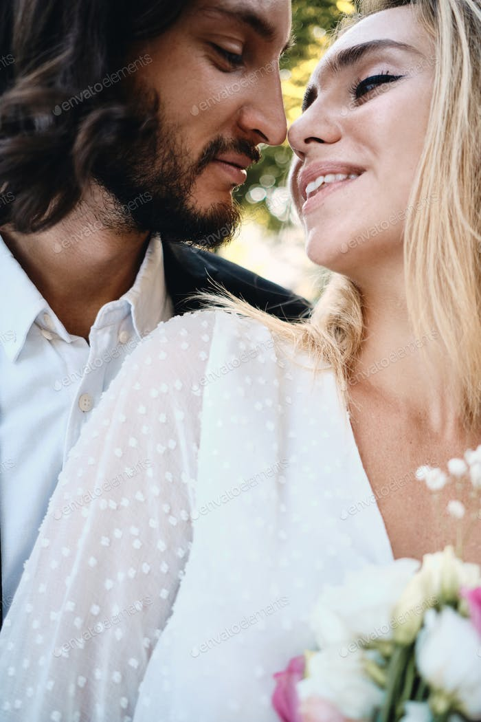 Portrait of beautiful bride and handsome groom dreamily kissing outdoor
