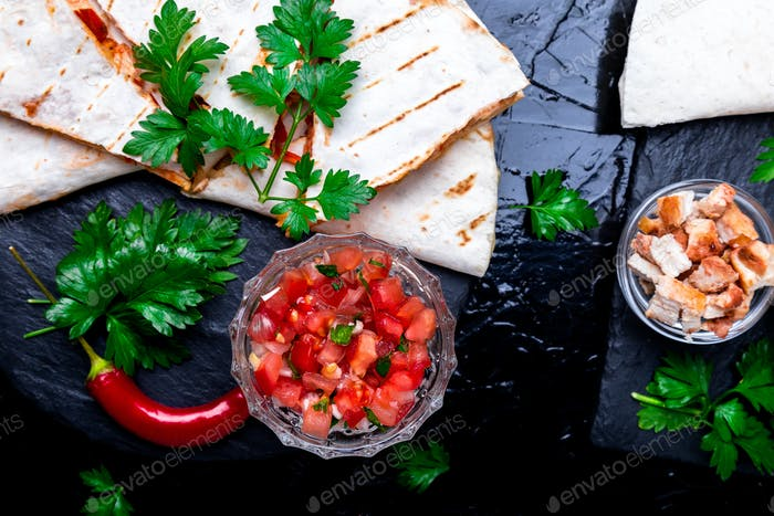 Mexican quesadilla and ingredients with salsa on black slate stone plate. Top view.