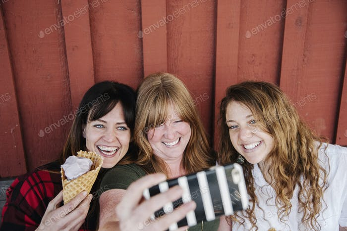 Three women eating ice cream, taking a selfie with a cell phone.