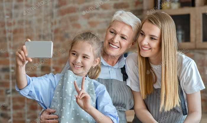 Cute little girl taking selfie with mom and granny
