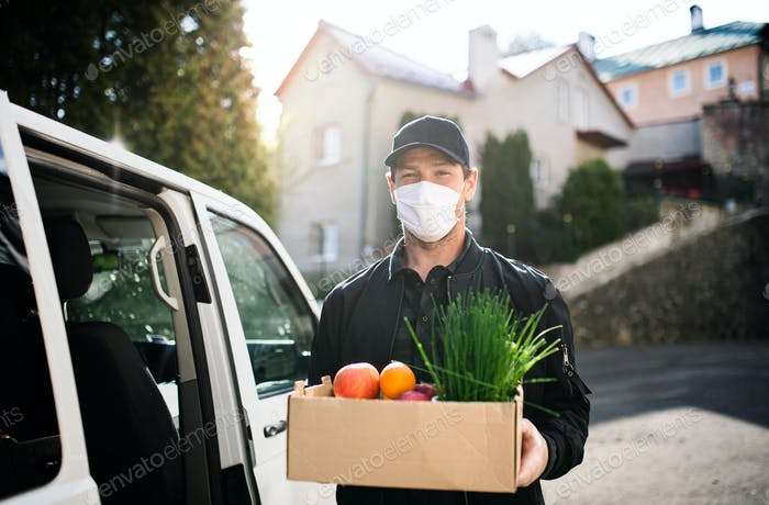 Delivery man courier with face mask delivering groceries in town
