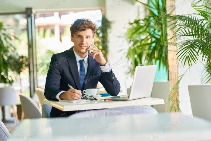 Successful Businessman Working in Cafe