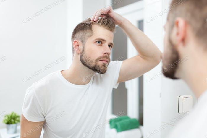 Schöner junger Mann besorgt über Haarausfall