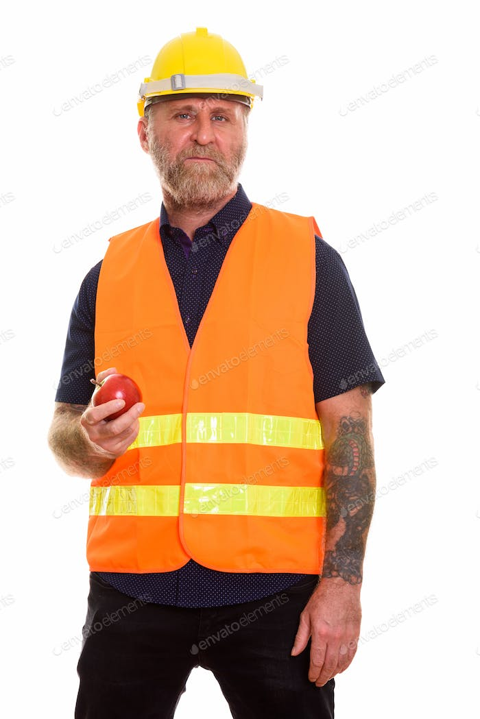 Mature bearded man construction worker holding apple