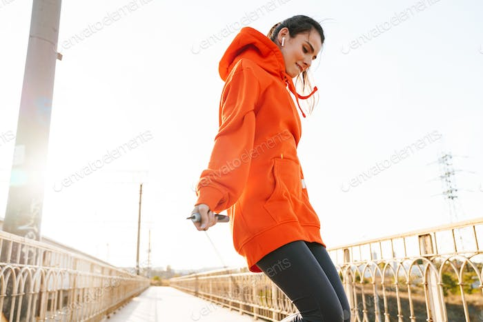 Woman outdoors make exercise with skipping jumping rope.
