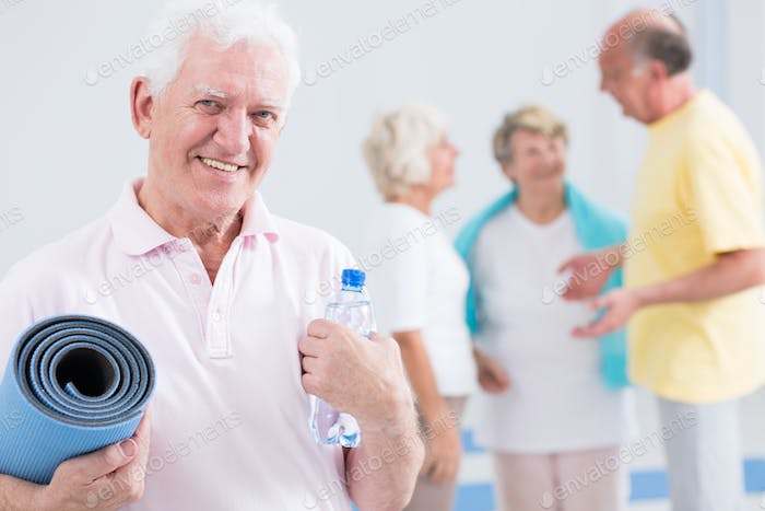 Man holding exercise mat and bottle of water