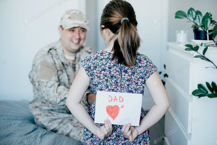 Happy father's day. Child daughter congratulates dad and gives him postcard. Family togetherness