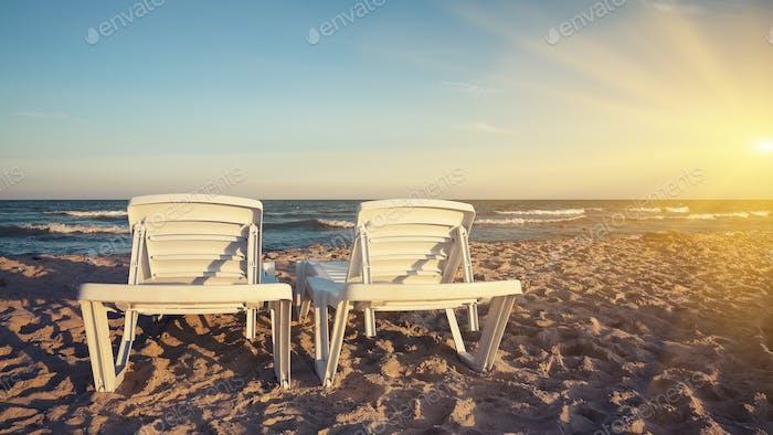 Zwei Liegestühle am Strand mit hellen Sonne und Wellen