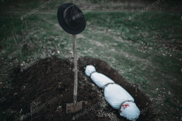 Grave with maniac victim wrapped in a canvas
