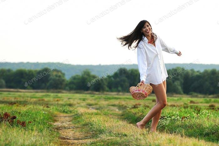 Girl dancing in field with basket in hands