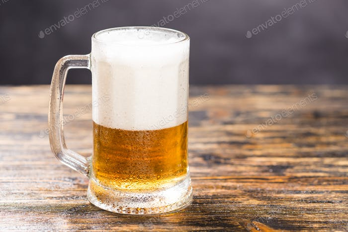 Cold glass of lager beer with foam and dew on dark background