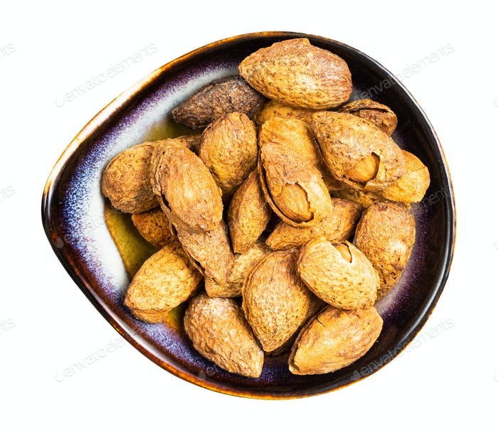 cracked almond drupes in ceramic bowl isolated