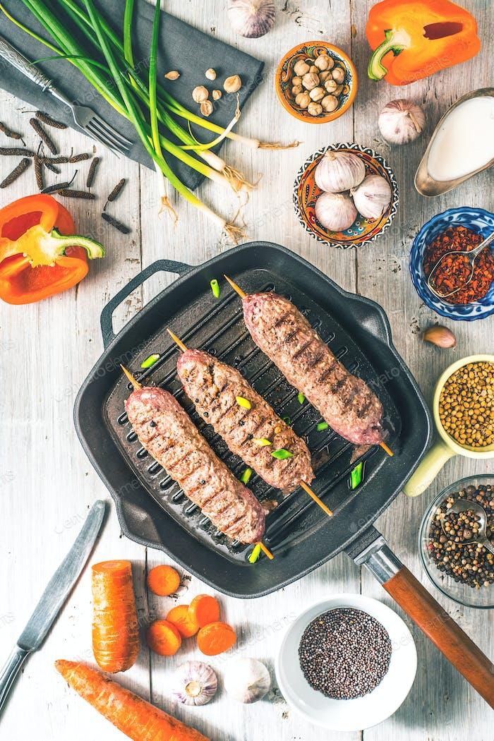Kebabs mit Gewürzen und Gemüse auf dem weißen Holztisch.