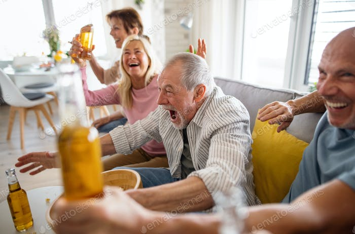 Group of senior friends watching movie indoors, party, social gathering and having fun concept