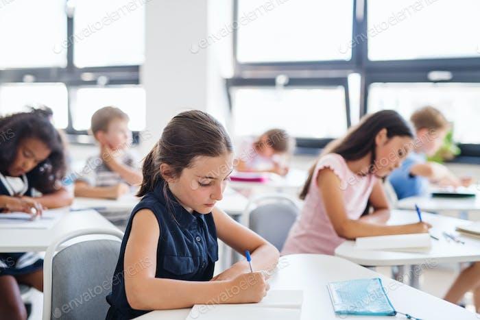 Konzentrierte kleine Schulkinder sitzen am Schreibtisch im Klassenzimmer, schreiben.