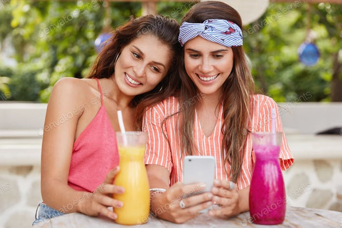 Photo of happy young women have samesex relations, surf internet on mobile phone, read comments unde