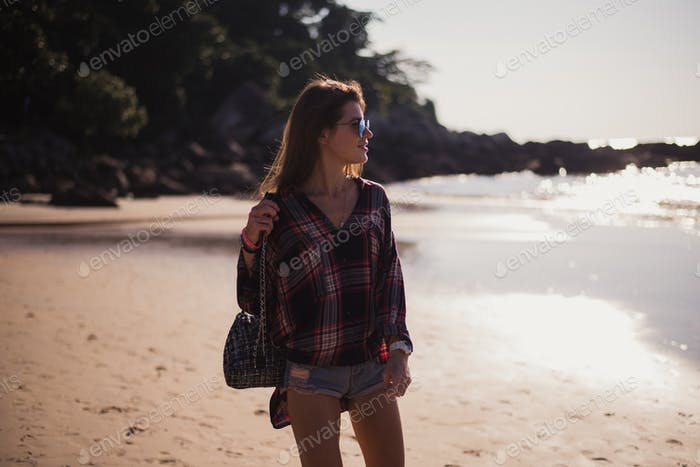 Summer sunny lifestyle fashion portrait of young stylish hipster woman walking on beach,wearing cute