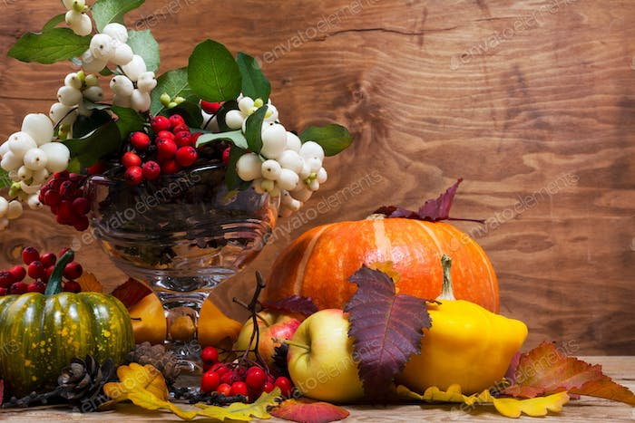 Thanksgiving arrangement with snowberry and rowan in glass vase,