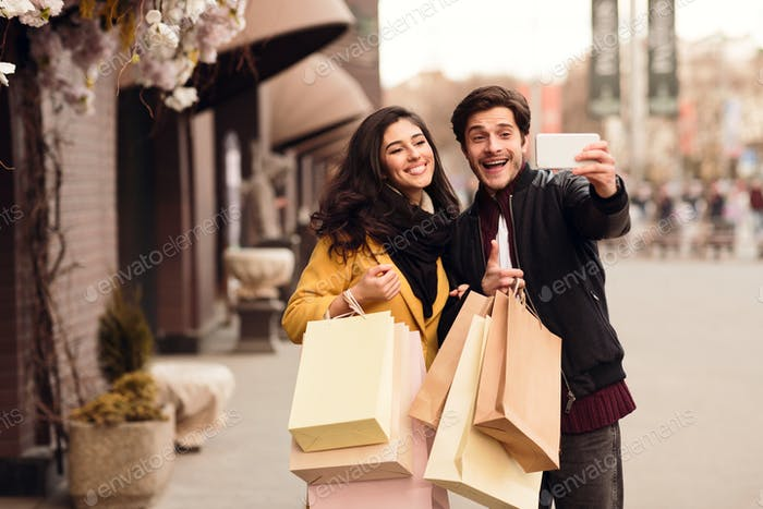Couple recording video for fashion blog after shopping in mall
