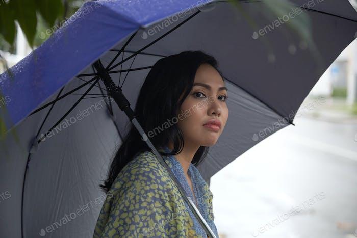 Filipino woman with umbrella looking away