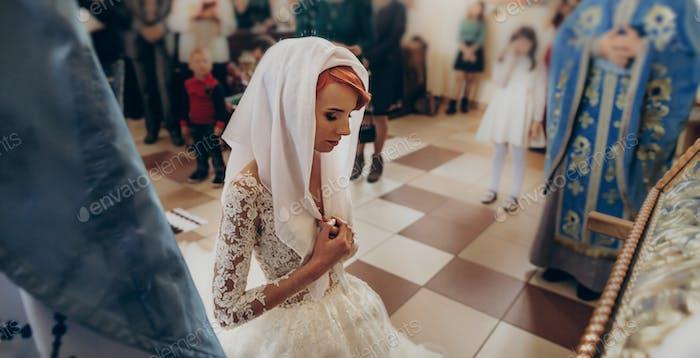 Stilvolle Braut beten während der Eheschließung in der Kirche