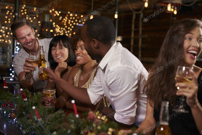 Friends enjoying a Christmas party at a bar making a toast