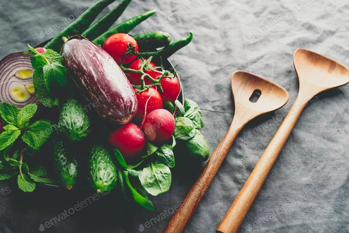 Different fresh colorful vegetables in a plate with wooden kitchen utensils on a table
