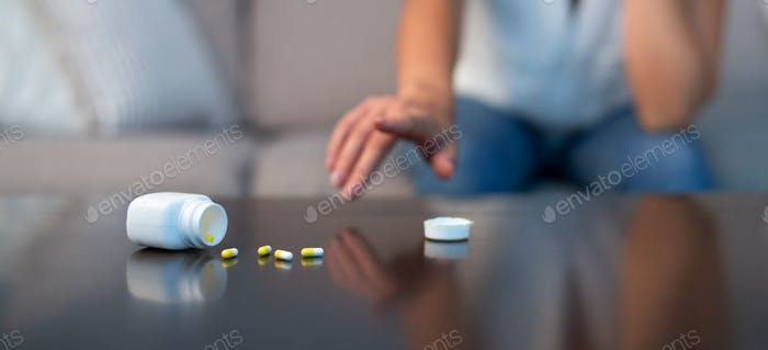 Unrecognizable Girl Reaching For Sleeping Pills Sitting On Couch Indoor