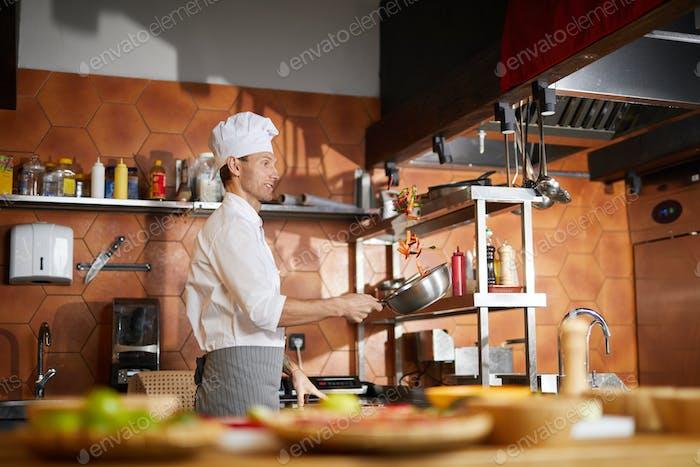 Chef cocina verduras en la cocina del restaurante