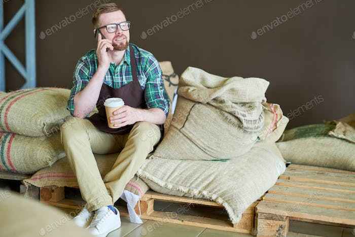 Modern Barista Sitting on Bags with Coffee