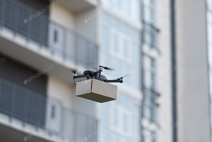 Quadrocopter delivering parcel through the city, coronavirus