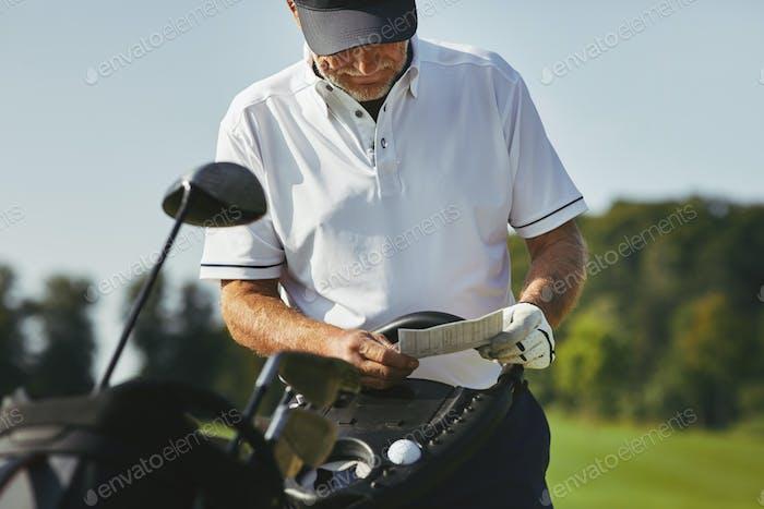 Senior Mann liest seine Scorecard während des Golfspiels