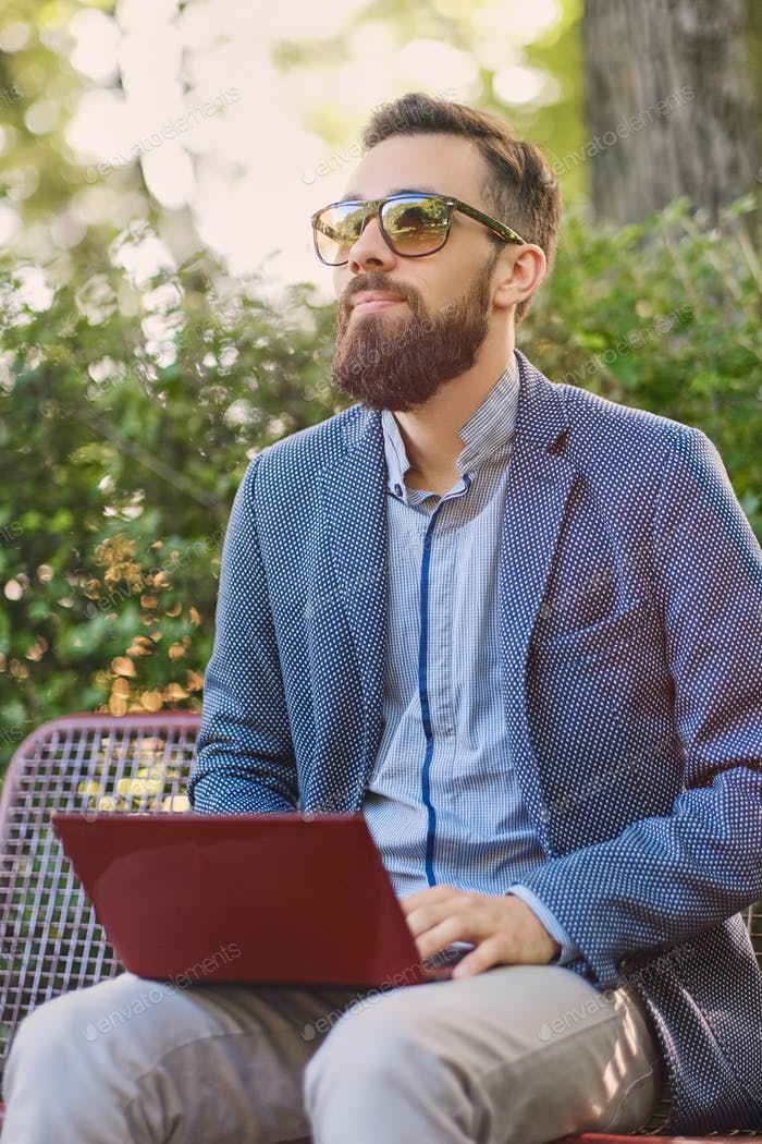 Handsome bearded male using laptop in a park.