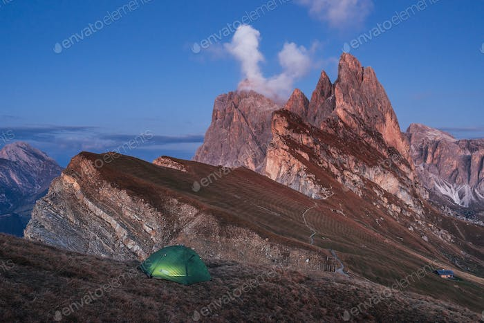 Evening and fog. Green tent standing on the hill. Awesome place in the alpes of Seceda