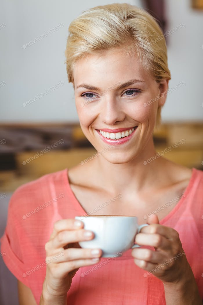 Pretty blonde woman holding a cup of coffee at home