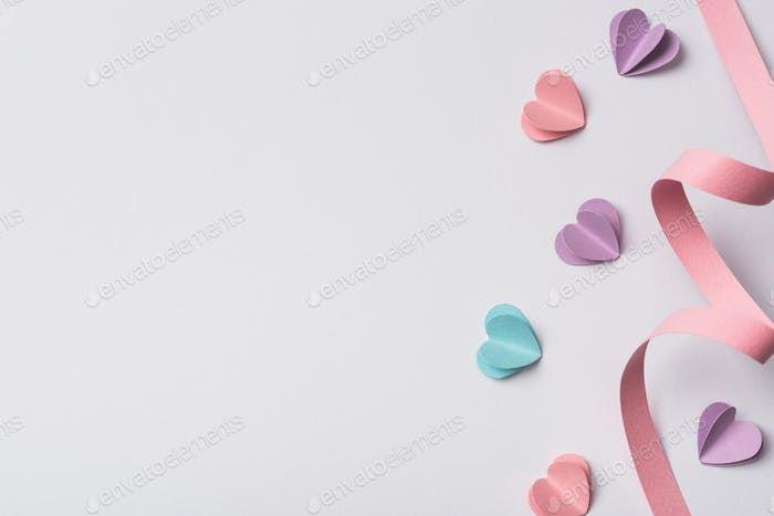 top view of small paper hearts and pink paper swirl on white background