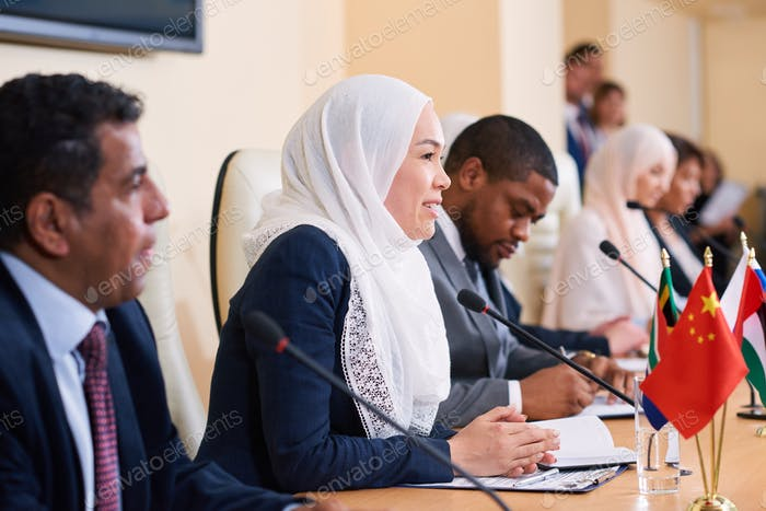 Young successful female delegate in hijab taking part in discussion